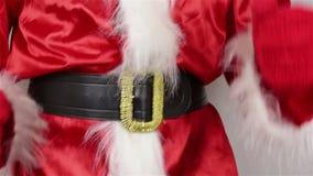 De kerstman past zijn riem rond zijn maag aan stock footage