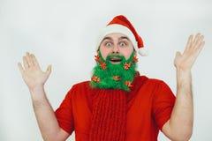 De Kerstman in rode kleren met groene baardglimlachen Stock Fotografie