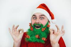 De Kerstman in rode kleren met groene baardglimlachen Stock Afbeeldingen