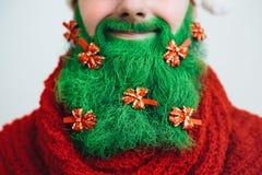 De Kerstman in rode kleren met groene baardglimlachen Stock Foto's
