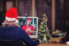 De kerstman verzendt online groeten naar de jonge mens Royalty-vrije Stock Afbeelding