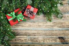 De Kerstmisachtergrond met giftdoos en de spar vertakken zich op houten rustieke raad, feestelijk sneeuweffect, Kerstmiskader Stock Fotografie
