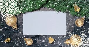 De Kerstmisachtergrond met spar vertakt zich, sneeuwvlokken en gouden ballen op rustieke houten lijst Hoogste mening met brief en stock video