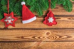 De Kerstmisachtergrond met de spartak en rood van de Kerstmanhoed voelde decoratie over donkere houten planken royalty-vrije stock foto's