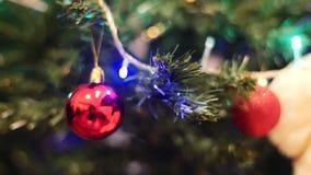 De Kerstmisballen hangen op de Kerstboom De decoratieve slinger glanst op de Kerstboom stock footage