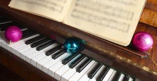 De Kerstmisdecoratie liggen op een piano stock fotografie