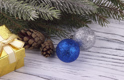 De Kerstmisdecoratie met gouden blauwe en zilveren de ballen natuurlijke spar van de giftdoos vertakt zich kegels op witte houten Stock Afbeeldingen