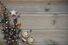 De Kerstmisfotografie met het zilveren en goud gekleurde ornament van de eikelboom op natuurlijke rustieke houten achtergrond met stock fotografie