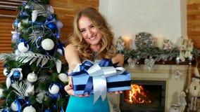 De Kerstmisgift, portret van wijfje met Kerstmisgift ter beschikking, meisje geeft een feestelijk verpakt heden, op Kerstavond stock videobeelden