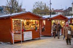 De Kerstmismarkt bij nacht tijdens de feestelijke periodeverkopers verkoopt van tijdelijke houten chalets Royalty-vrije Stock Afbeelding