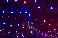 De Kerstmisslinger steekt achtergrond aan Stock Foto