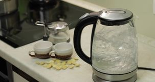 De ketel van de thee met kokend water Theezakjes en suiker op de achtergrond stock footage