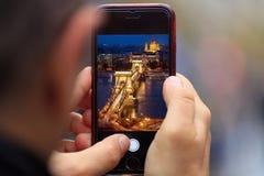 De kettingsbrug in het beeld van Boedapest verschijnt op tablet, smartphone in mensen` s handen Vage achtergrond Stock Afbeeldingen
