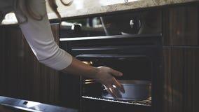 In de keuken zet een vrouw een container in een oven stock afbeelding
