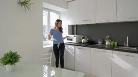 De keukenpret, het vrolijke huisvrouwenvrouw dansen en zingt met pan in handen terwijl thuis het koken van maaltijd bij keuken stock videobeelden
