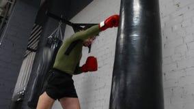 De Kickboxingsvechter leidt in een gymnastiek op uitoefenend sommige schoppen en stempels met ponsenzak stock video