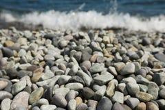De kiezelsteenstenen en met getijde droegen van overzees op achtergrond Royalty-vrije Stock Foto's