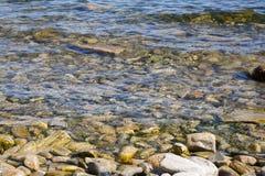 De kiezelsteenstenen zijn rotsachtige glad in water dichtbij de kust stock foto's