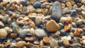 De kiezelstenen op het overzeese strand wordt gewassen door de overzeese branding, close-up Textuur van overzeese kiezelstenen, m stock videobeelden