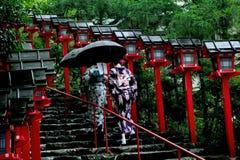 2 de kimonodames worstelden door regen aan maatregel van geloof Stock Fotografie