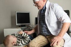 De kind arts onderzoekt de patiënten in zijn bureau De gelukkige kinderen zijn zeer dierbaar van een goede pediater Het concept e Royalty-vrije Stock Fotografie