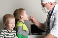 De kind arts onderzoekt de patiënten in zijn bureau De gelukkige kinderen zijn zeer dierbaar van een goede pediater Het concept e Stock Foto's