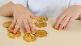 De kind` s handen spelen met gouden muntstukken van bitcoins op de lijst De kindspelen met een crypto munt Close-up stock videobeelden