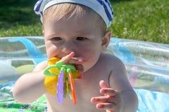 De kind` s tanden worden gesneden De eerste tanden worden gesneden, tegen de achtergrond van groen gras Stock Foto's