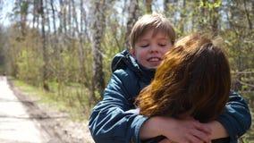 De kind-zoon looppas om zijn moeder te ontmoeten, koestert haar zacht Gelukkige familie, houdende van ouders stock video