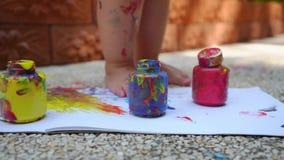 De kindbenen trekt een blauw, rood en gele vingerverf - op een wit blad van document Creatieve kindontwikkeling binnen stock footage