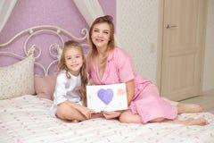 De kinddochter wenst mamma geluk en geeft haar een prentbriefkaar royalty-vrije stock afbeeldingen
