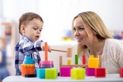 De de kinderdagverblijfbaby en verzorger spelen met montessorispeelgoed bij lijst in opvangcentrum stock foto