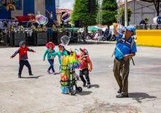 De kinderen achtervolgen reuzediebellen door de verkoper van het bellentoverstokje worden gecreeerd Royalty-vrije Stock Fotografie