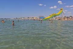 De kinderen baden in het duidelijke water van de Zwarte Zee bij het strand ` Rodnichok ` in de toevluchtstad van Evpatoria Royalty-vrije Stock Afbeeldingen