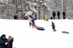 De kinderen beklimmen een sneeuwheuvel royalty-vrije stock fotografie