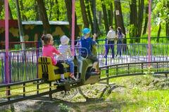 De kinderen berijden op de carrousel op de speelplaats van de kinderen Stock Afbeeldingen