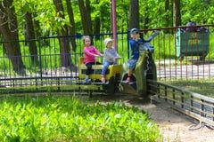 De kinderen berijden op de carrousel op de speelplaats van de kinderen Royalty-vrije Stock Afbeeldingen