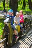 De kinderen berijden op de carrousel op de speelplaats van de kinderen Stock Afbeelding