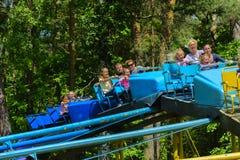 De kinderen berijden op de carrousel op de speelplaats van de kinderen Stock Foto