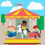 De kinderen berijden op de carrousel Stock Afbeelding