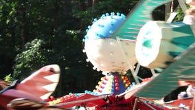 De kinderen berijden op de carrousel in het park, berijden de kinderen op vliegtuigen stock footage