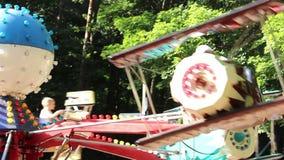 De kinderen berijden op de carrousel in het park, berijden de kinderen op vliegtuigen stock videobeelden