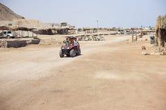 De kinderen berijden op de Woestijn van de vierlingfiets stock fotografie