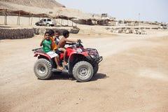 De kinderen berijden op de Woestijn van de vierlingfiets stock foto