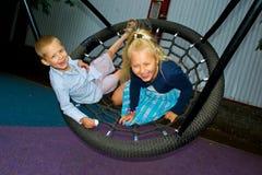 De kinderen berijden op een schommeling Stock Foto's