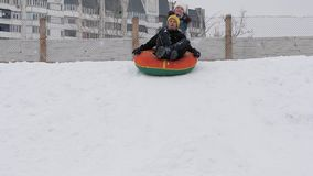 De kinderen berijden in de winter met een buizenstelseldia stock footage