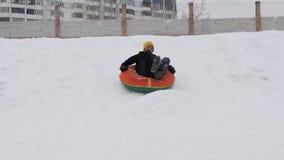 De kinderen berijden in de winter met een buizenstelseldia stock video