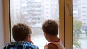 De kinderen bevinden zich bij het venster en letten op de sneeuw dalend op de straat Eerste dag van de winter stock videobeelden
