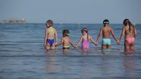 De kinderen bevinden zich in de handen van de waterholding stock video