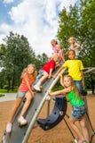 De kinderen bij de speelplaatsbouw spelen samen Stock Fotografie